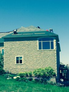 Re-Roof Omaha Nebraska our guys working on laying felt on a roof