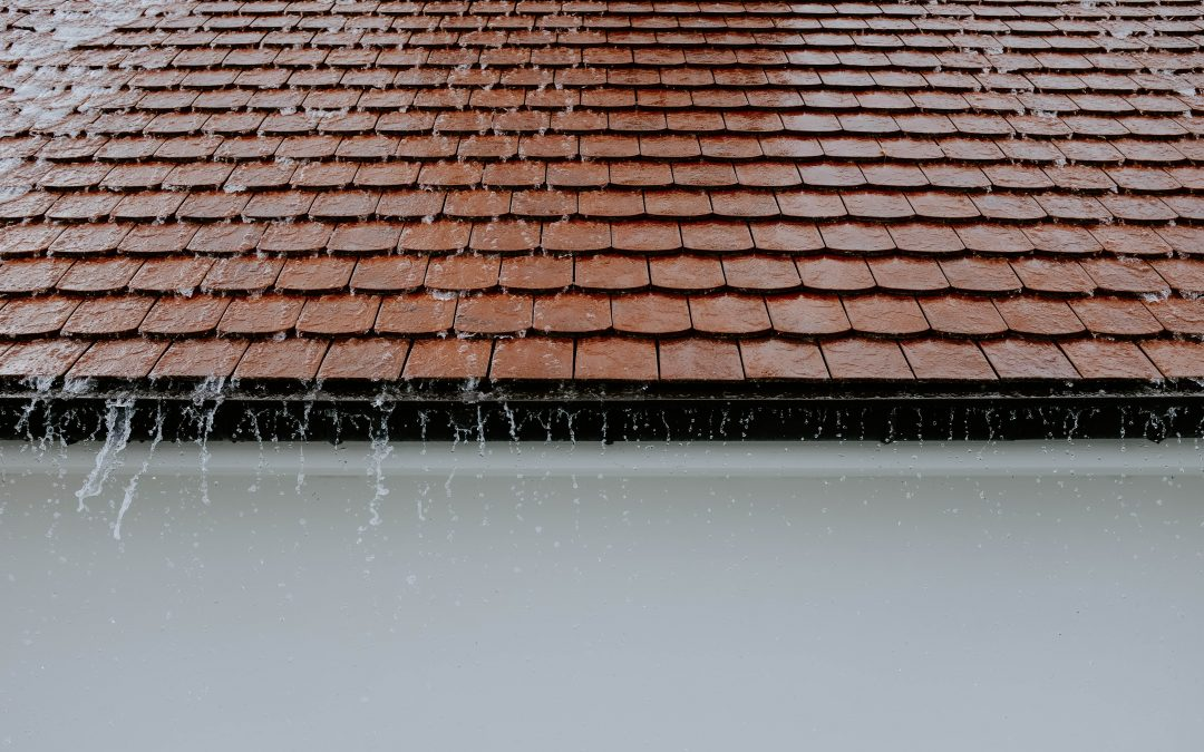 rain rushing off of a red tiled roof