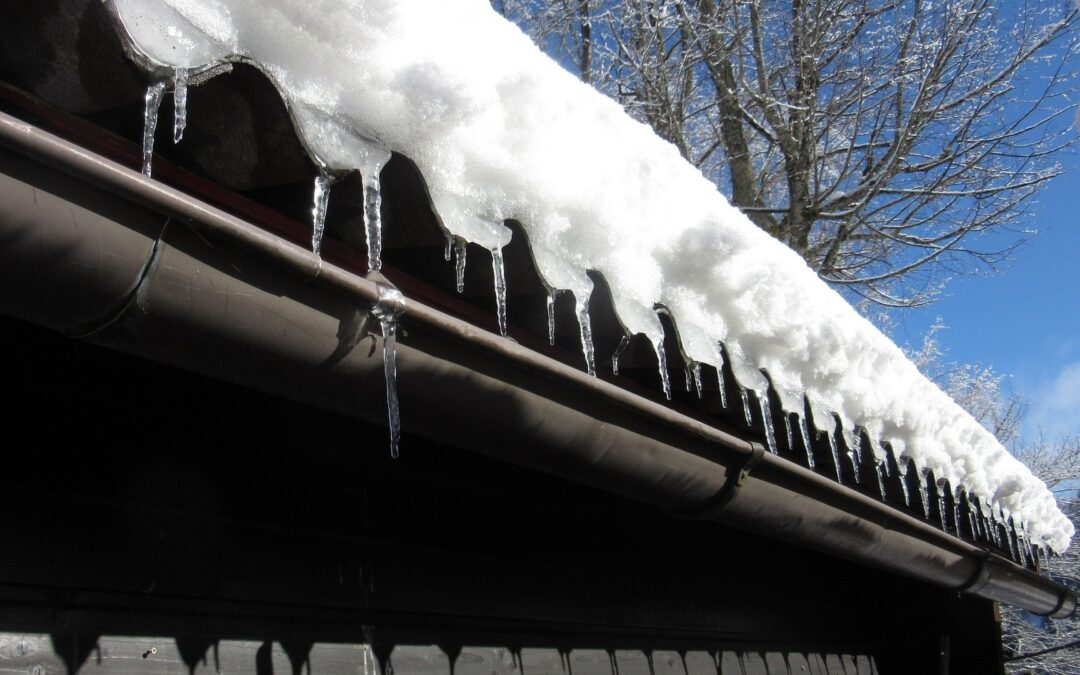 snow and icicles handing off edge of home's roof