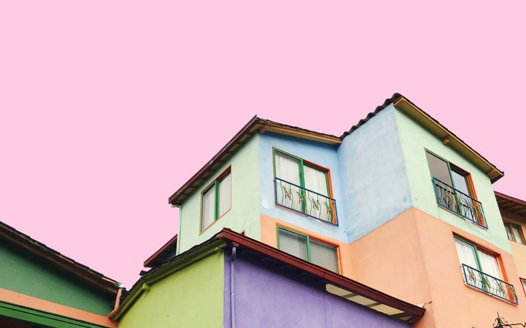 apartment building painted in bright pastel colors against a light pink sky